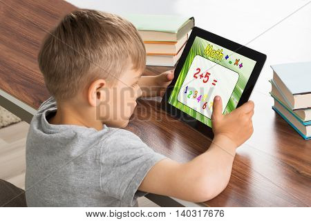 Pupil Solving Math Problem On Digital Tablet With Stack Of Books On Desk
