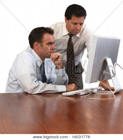two men looking at a computer screen, one sitting the other leaning over with a white background