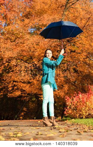 Happiness freedom and people concept. Casual young woman teen girl walking relaxing with blue umbrella in autumnal park outdoor