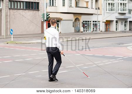 Young Blind Man Holding Stick Crossing Road