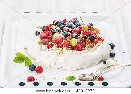 Homemade Pavlova cake with fresh garden and forest berries on white baking tray over white painted wooden background, selective focus, horizontal composition