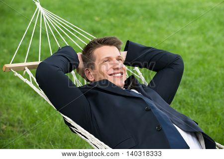 Happy Young Businessman Lying In Hammock At Park