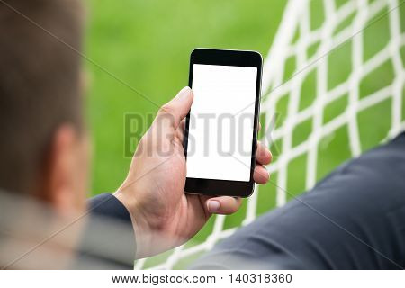 Close-up Of Person's Hand In Hammock Holding Mobile Phone With Blank Screen