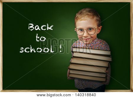 Excited boy with books near school chalkboard