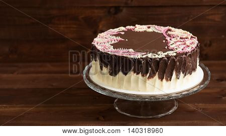 Sponge cake with mehendi patterns on the glass stand. Wooden background.