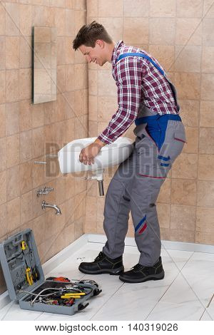 Side View Of Happy Male Plumber Installing Sink In Bathroom