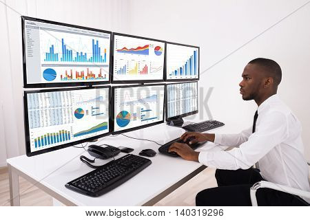 Young Businessman Analyzing Financial Chart On Multiple Computers In Office