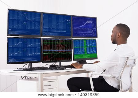 Businessman Analyzing Data Displayed On Multiple Computer Screens In Office