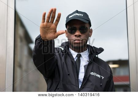 Confident Young African Male Security Guard Making Stop Gesture