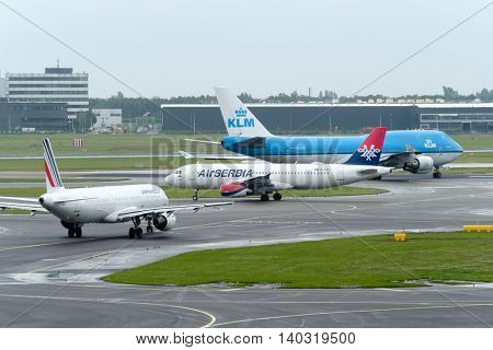 Amsterdam - July 1, 2016: Aircrafts of different airlines moving on runways at Amsterdam airport in the daytime