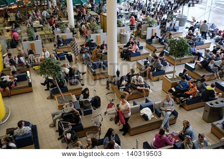 Amsterdam - July 1, 2016: People visit departure hall in international Schiphol airport at day time