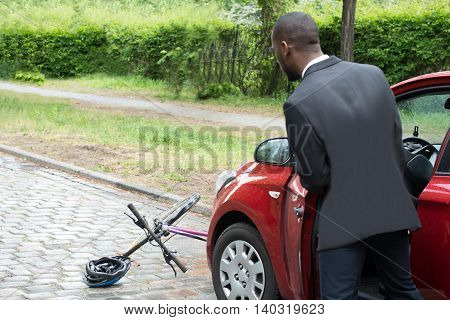 Rear View Of A Young African Male Driver Looking At Bicycle After Collision On Street