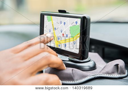 Close-up Of Person's Hand Using GPS Service While Driving Car