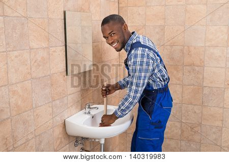 Happy Young African Male Plumber Using Plunger In Bathroom Sink