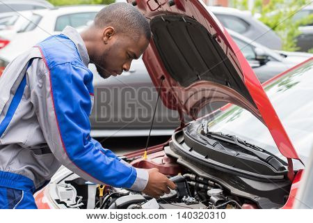 Close-up Of Male Mechanic Checking Car Battery Level With Multimeter