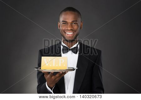 Happy African Waiter Holding Tray With VIP Sign