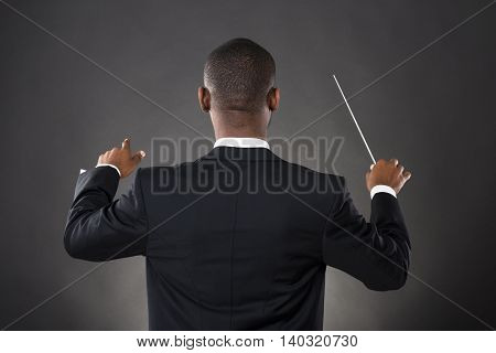 Young African Conductor Directing With His Baton Against Black Background