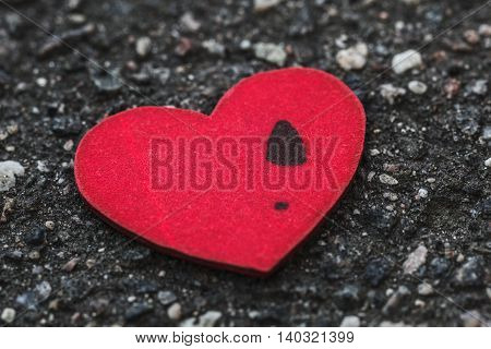 Lonely man's heart with a women's footprint lying on asphalt. Concept of breakup long relations