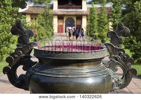 Incense stick in a copper pot at a Buddhist pagoda in Asia