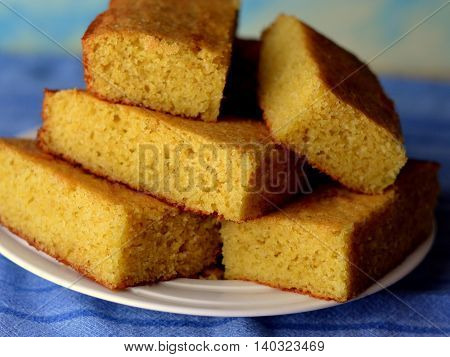 Close-up of Cornbread, cut into squares and stacked on a white plate. Set on a blue tablecloth with blue behind.