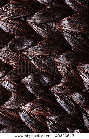 Closeup dark brown wicker woven pattern for abstract background or texture