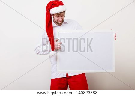 Man in santa claus hat holding empty blank banner with copy space. Handsome guy in studio on gray. Christmas xmas advertisement.