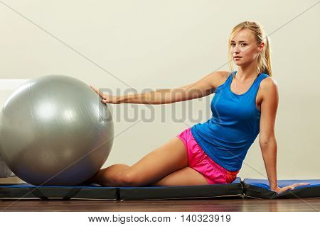 Sport training gym and lifestyle concept. Young attractive slim woman in sportswear doing fitness exercises with fit ball at home