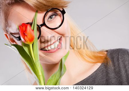 People and nature. Young woman with tulip on her face live in peace with floral world. Girl feel connection to natural environment.