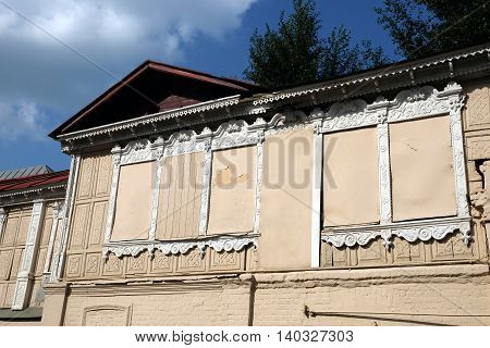 Facade of old vintage house with boarded up windows in rural city horizontal photo closeup