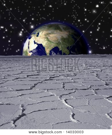 Earth rising over a lunar landscape
