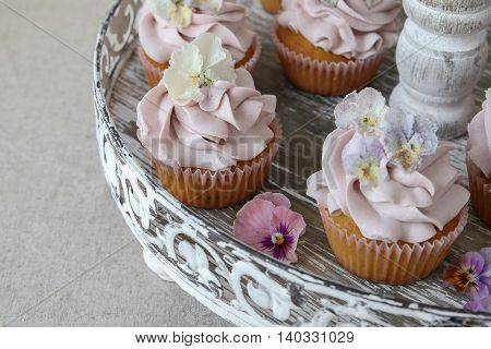 Purple Cupcakes With Sugared Edible Flowers On Vintage Cake Stand.