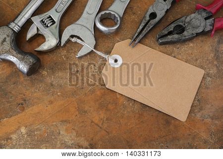 Different Tools On Rustic Wooden Worktop With Brown Tag