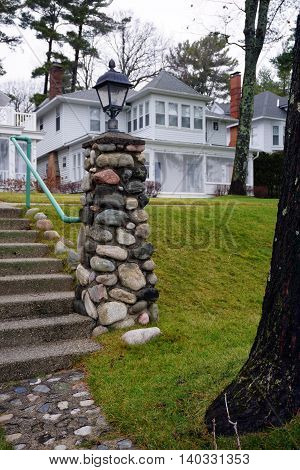 WEQUETONSING, MICHIGAN / UNITED STATES - DECEMBER 22, 2015:  A stone lamppost stands at the end of a cement stairway in Wequetonsing, Michigan.