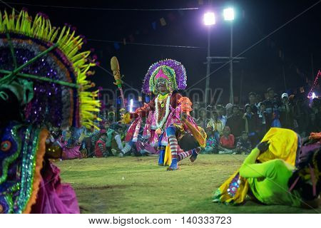 BAMNIA PURULIA WEST BENGAL INDIA - DECEMBER 23RD 2015 : Dancer dressed as Hanumanji is jumping on air Chhau Dance festival. It is a very popular Indian tribal martial dance performed at night amongst spectators.