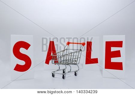 Sale labels and old model shopping trolley on White background conceptual image
