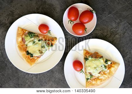 Pizza slice and red tomatoes on plates.