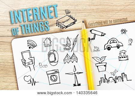 Open Notebook on wooden desk with sketch icon doodle with Internet of Things (IOT) Technology concept