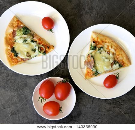 Pizza on white plates with red tomatoes.