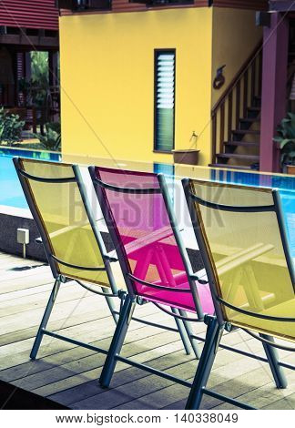 three deck chairs by the side of a pool