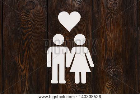 Paper couple in love. Wooden background. Abstract conceptual image