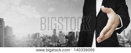 Businessman extending hand with panoramic cityscape of business district in the city
