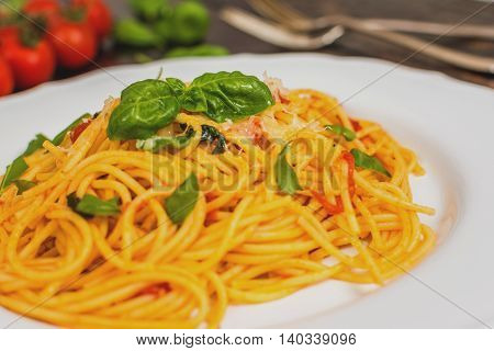 Traditional italian cuisine spaghetti with tomato sauce basil and cheese on dark wood table