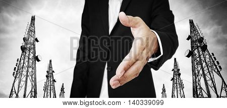 Businessman extending hand with Telecommunication towers with TV antennas and satellite dish