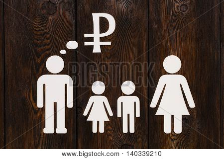 Paper family parents are thinking about money. Wooden background. Abstract conceptual image