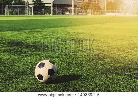 Old soccer ball on green grass, vintage tone with bright sunlight