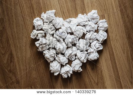 Heart shape made of crumpled paper, on wooden background