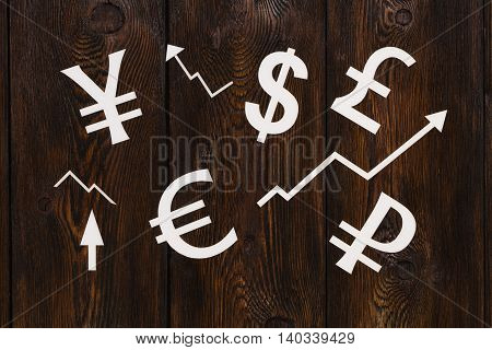 Paper currency signs money. Wooden background. Abstract conceptual image