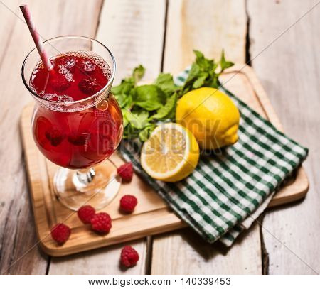 Ice cold beverage glass with raspberry lemon cocktail . Alcohol country cocktail beverage number two hundred ninety seven with raspberry on checkered napkin outdoor . Top view on wooden boards.
