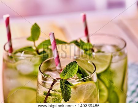 Alcohol drink. On wooden boards part of three glasses with alcohol drink and ice cubes. Drink number two hundred ninety-two cocktail mohito with mint leaf. Top view. Country life. Light background.