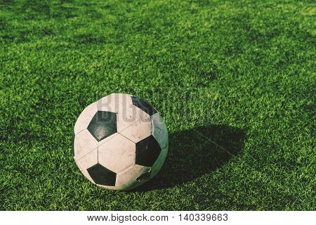 Old soccer ball on green grass, vintage tone
